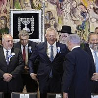 Prime Minister Benjamin Netanyahu approaches rival Benny Gantz as they and other party leaders including Avigdor Liberman and Aryeh Deri prepare to pose for a group picture during the swearing-in of the 22nd Knesset in Jerusalem, on October 3, 2019. (Hadas Parush/Flash90)