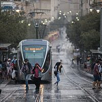 People walk in rainy and windy weather on Jaffa street in Jerusalem, on October 15, 2019. (Yonatan Sindel/Flash90)