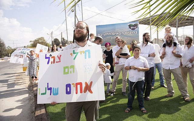 """Yitzhar residents protest in support of IDF soldiers at the entrance to the Samaria Brigade, October 20, 2019, following an attack on Israeli soldiers near the northern West Bank settlement overnight. The sign reads: """"IDF soldiers are our brothers."""" (Sraya Diamant/Flash90)"""