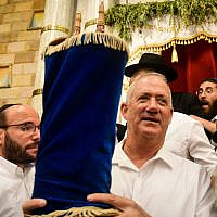 Blue and White party chairmen Benny Gantz carries a Torah scroll as he dance during Simhat Torah celebrations in Kfar Chabad, on October 21, 2019. (Yossi Zeliger/Flash90)