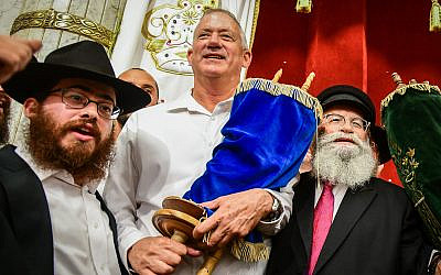 Blue and White party chairmen Benny Gantz carries a Torah scroll as he dances during Simhat Torah celebrations in Kfar Chabad, on October 21, 2019. (Yossi Zeliger/Flash90)