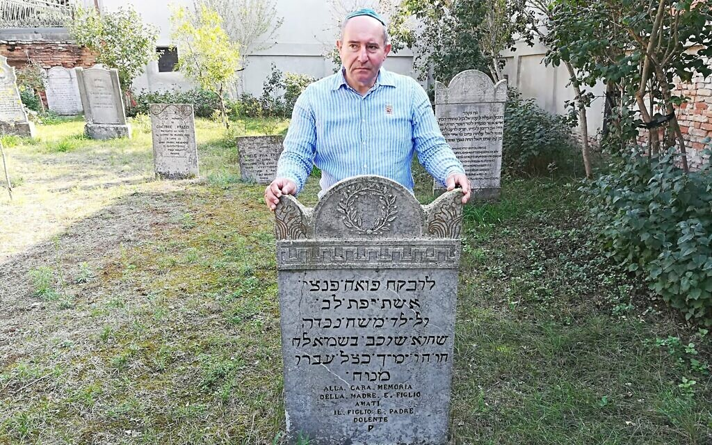 Giuseppe Minera next to a tombstone in the Jewish cemetery of Ostiano, Italy. (Giovanni Vigna/ Times of Israel)