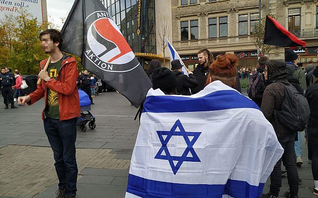 Protestors wear an Israeli flag and IDF t-shirt in Halle, Germany's central Marktplatz, October 11, 2019. (Yaakov Schwartz/ Times of Israel)
