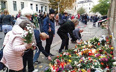 People place flowers in front of the synagogue in Halle, Germany, where a memorial has been placed for the victims of Wednesday's shooting. October 11, 2019. (Yaakov Schwartz/ Times of Israel)