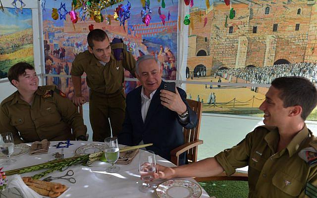 From left to right:  Cpl. Aleksandra Vodenskov, Sgt. Alexander Sachs, Prime Minister Benjamin Netanyahu and Sgt. Eddie Laufer in the prime minister's sukkah in Jerusalem, October 13, 2019 (Koby Gideon/GPO)