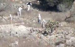 Masked settlers near Givat Ronen hurl stones at Palestinian farmer on October 19, 2019. (Screen capture/Yesh Din)