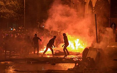 Lebanese demonstrators stand by a fire a make-shift barricade amid clashes with security forces during a mass protest at Riad al-Solh Square in Beirut on October 18, 2019. (STR/AFP)