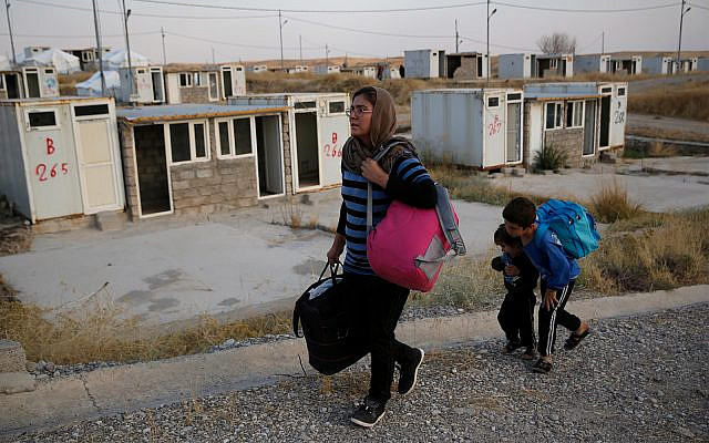 Salwa Hanna with her children, who are newly displaced by the Turkish military operation in northeastern Syria, carry their belongings after they arrive at the Bardarash refugee camp, north of Mosul, Iraq, October 17, 2019. (AP Photo/Hussein Malla)