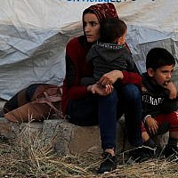 A Syrian woman with her children, who were displaced by the Turkish military operation in northeastern Syria, wait to receive a tent and other aid supplies at the Bardarash refugee camp, north of Mosul, Iraq, October 17, 2019. (AP Photo/Hussein Malla)