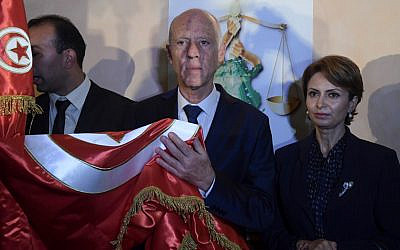 Conservative academic Kais Saied, center, flanked by his wife Ichraf Chebil, right, celebrates his victory in the Tunisian presidential election in the capital Tunis on October 13, 2019. (Fethi Belaid/AFP)