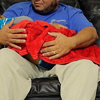 """A migrant toddler is cradled by a Comprehensive Health Services, Inc. caregiver at a """"tender-age"""" facility for babies, children and teens, in Texas's Rio Grande Valley, August 29, 2019, in San Benito, Texas. (AP Photo/Eric Gay)"""