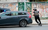 A police officer runs on a road in Halle, Germany, following a  shooting outside a synagogue, October 9, 2019. (Sebastian Willnow/dpa via AP)