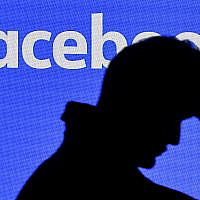 Illustrative: A man passes a Facebook screen at the Gamescom gathering in Cologne, Germany, August 20, 2019. (AP Photo/Martin Meissner)