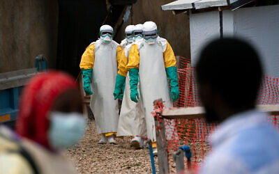 Illustrative: Health workers dressed in protective gear begin their shift at an Ebola treatment center in Beni, Congo DRC, July 16, 2019. (AP Photo/Jerome Delay)
