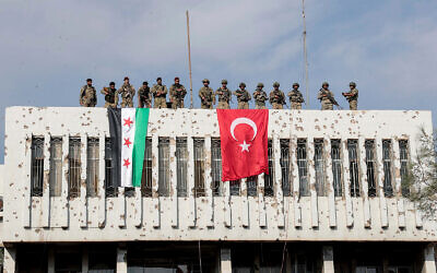Turkish soldiers, right, and Turkey-backed opposition fighters, left, stand on a building next to their flags the town of Ras al Ayn in northeastern Syria, October 23, 2019. (Ugur Can/DHA via AP)