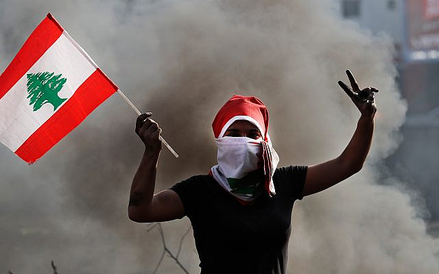 An anti-government protester holds a Lebanese flag and flashes the victory sign near Beirut, Lebanon, October 20, 2019. (AP Photo/Hussein Malla)