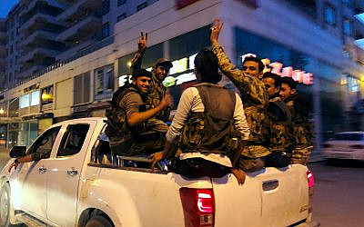 Turkish-backed Syrian opposition fighters from the Syrian National Army drive through the town of Akcakale, Sanliurfa province, southeastern Turkey, on their way to cross the border to Tel Abyad, Syria, October 11, 2019. (AP Photo/Emrah Gurel)