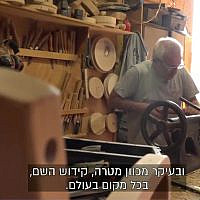 A worker in Kibbutz Lavi's carpentry factory. (Screenshot/Channel 13)