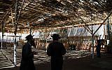 Illustrative: Jews in a sukkah in Jerusalem, September 21, 2015. (Nati Shohat/Flash90)