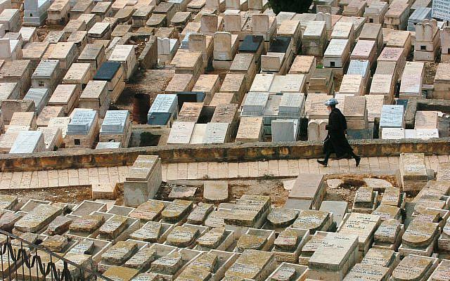 ILLUSTRATIVE -- A man walks through a cemetery in Jerusalem (Nati Shohat /Flash90)