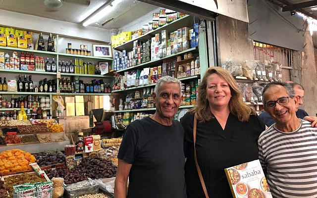 Cookbook author Adeena Sussman (center) with a copy of 'Sababa' and the Amrani brothers in the Carmel Market (Jessica Steinberg/Times of Israel)