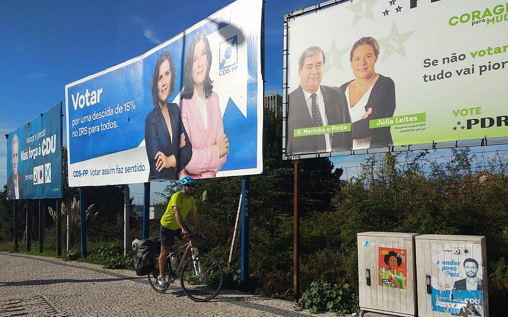 A cyclist passes by signs for Portuguese political parties during national elections in Porto, Portugal, on October 6, 2019. (Melanie Lidman/Times of Israel)