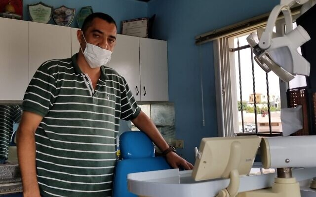 Ameen Mansour, a 47-year-old dentist from the village of Azzun, standing in his clinic on October 20, 2019. (Adam Rasgon/Times of Israel)