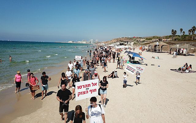 Surfers protest plans to install a breakwater at the last open beach in Tel Aviv, October 4, 2019. (eyesurf productions)