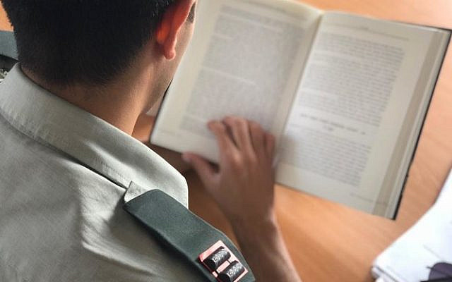 An illustrative photo released on October 16, 2019, showing an IDF officer reading a book. (Israel Defense Forces)