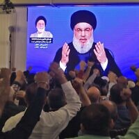 Supporters of Hassan Nasrallah, the head of Lebanon's Hezbollah terror group, watch him speak through a giant screen at a mosque in the Lebanese capital Beirut's southern suburbs on November 1, 2019. (AFP)