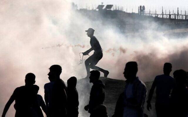 Palestinian rioters stand amid tear gas canisters fired by Israeli forces during clashes along the border with Israel east of Bureij in the central Gaza Strip on November 1, 2019. (Mahmud Hams/AFP)