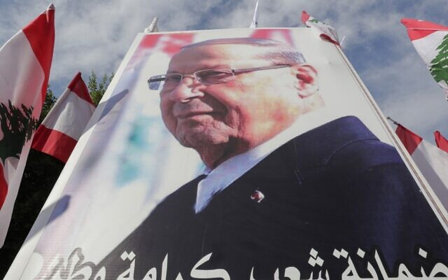 Supporters of Lebanese President Michel Aoun hold a poster of him during a counter-protest near the presidential palace in Baabda on November 3, 2019 (ANWAR AMRO / AFP)