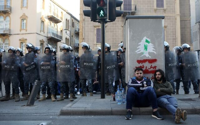 Lebanese anti-government protesters rest on a pavement in front of members of security forces in a central neighborhood of the capital Beirut on November 4, 2019 (Patrick BAZ / AFP)