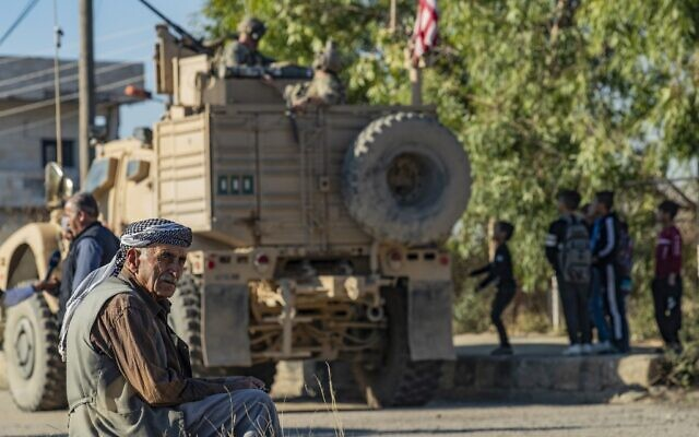 A Syrian man sits near a US armored vehicle on patrol in the village of Ein Diwar in Syria's northeastern Hasakeh province on November 4, 2019. (Delil SOULEIMAN / AFP)