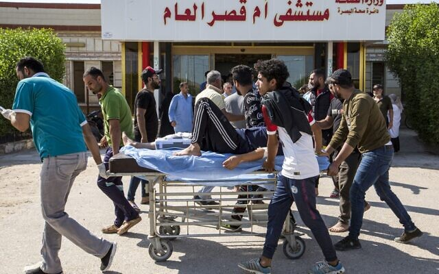 Iraqi youths push a man with an injured leg on a gurney outside the gate to Umm Qasr hospital in the southern Iraqi port city on November 5, 2019, after security forces attempted to break up crowds blocking the road to the port earlier in the day. (Photo by Hussein FALEH / AFP)
