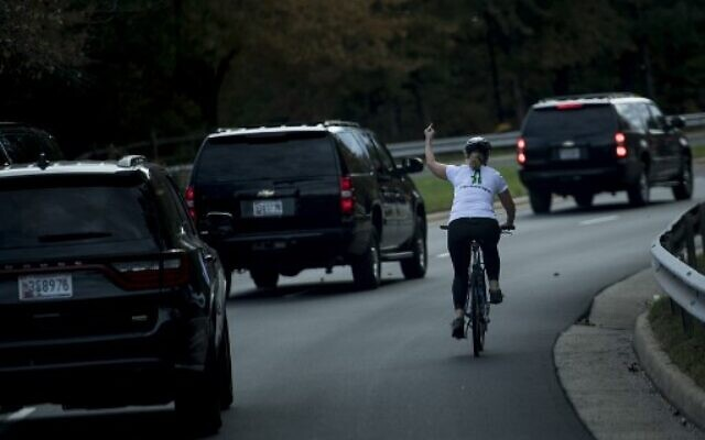 In this file photo taken on October 29, 2017 Juli Briskman gestures with her middle finger as a motorcade with US President Donald Trump departs Trump National Golf Course in Sterling, Virginia.  (Photo by Brendan Smialowski / AFP)