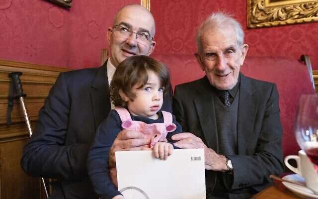 Two-year-old Emmy de Waal is held by her father John de Waall (L) and grandfather Victor de Waal during their reunion in Vienna, Austria on November 4, 2019. Ephrussi family members returned to Vienna in November for their first reunion in more than eight decades to attend the opening of an exhibition about their family story (JOE KLAMAR / AFP)