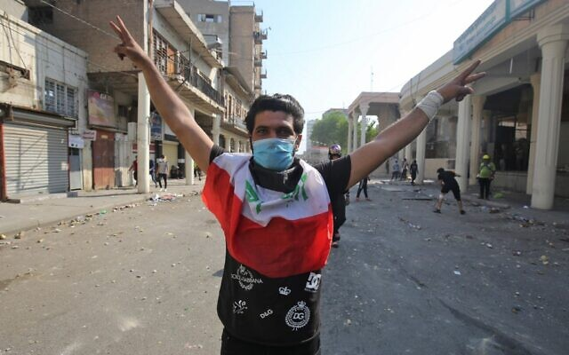 An Iraqi protester wearing a surgical mask gestures during clashes with security forces near the central bank in the capital Baghdad on November 7, 2019, amid ongoing anti-government protests. (AHMAD AL-RUBAYE / AFP)