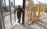 A picture taken on November 8, 2019, shows an Israeli soldier closing a border gate on the Israeli side of the border at the Jordan Valley site of Naharayim. (Menahem Kahana/AFP)