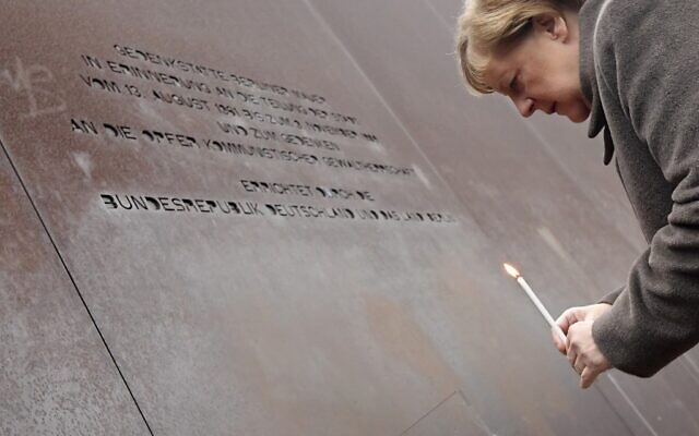 German Chancellor Angela Merkel places a candle at the Berlin Wall Memorial during the central commemoration ceremony for the 30th anniversary of the fall of the Berlin Wall, on November 9, 2019 (Tobias SCHWARZ / AFP)