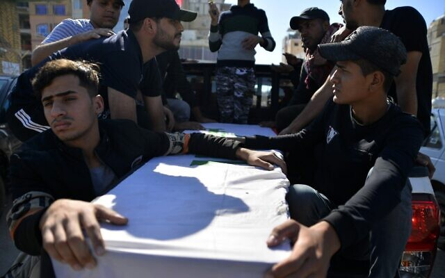 Mourners carry the casket of an Iraqi protester who was killed the day before during protests in the capital, during his funeral in the central Iraqi city of Najaf on November 10, 2019. (Haidar Hamdani/AFP)