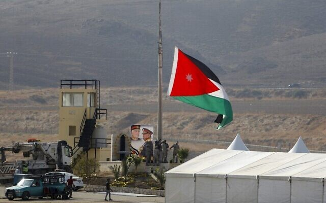 A picture taken from the Israeli side of the border shows Jordanian soldiers raising the national flag ahead of a ceremony at the Jordan Valley site of Naharayim, November 10, 2019. (Menahem Kahana/AFP)