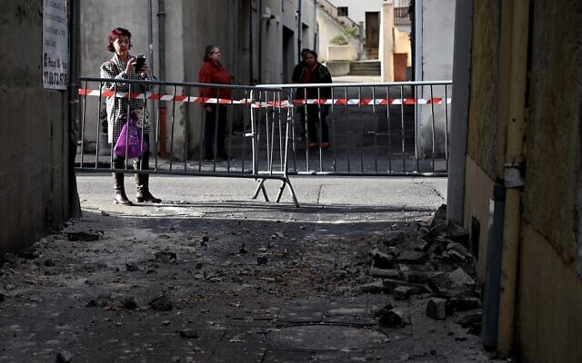 A woman takes a picture of bricks which fell from a wall in Le Teil, southeastern France, on November 11, 2019, after an earthquake with a magnitude of 5.4 hit the area. (Jeff Pachoud/AFP)
