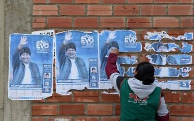 A woman removes posters of Bolivia's Evo Morales from the wall of a house in El Alto on November 11, 2019, a day after the resignation of the leftist leader as president. (Aizar RALDES / AFP)