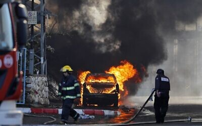 A vehicle parked in front of a factory that was hit with a rocket fired from the Gaza Strip catches fire in the southern town of Sderot on November 12, 2019.  (Ahmad Gharabli/AFP)