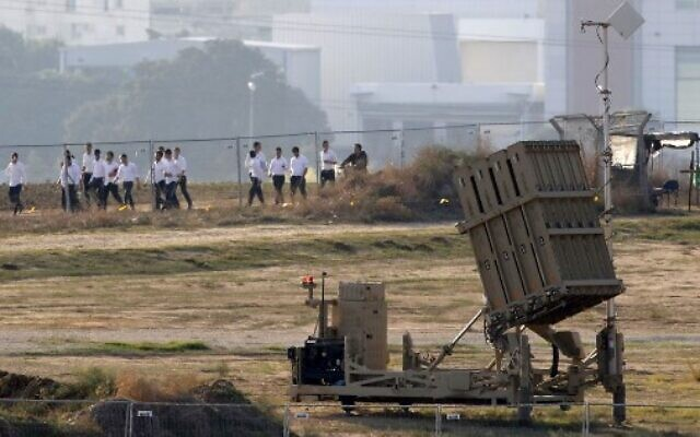 Israeli students walk past a battery of Iron Dome missile defense  system, designed to intercept and destroy incoming short-range rockets and artillery shells, in the southern Israeli city of Ashdod, neighbouring the Palestinian Gaza Strip, on November 12, 2019. (Photo by JACK GUEZ / AFP)