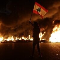 A Lebanese anti-government protester waves a Lebanese flag in front of burning tires that block the main highway linking the city of Tripoli to Beirut at the coastal city of Byblos, north of the capital on November 13, 2019.  (Photo by Joseph EID / AFP)
