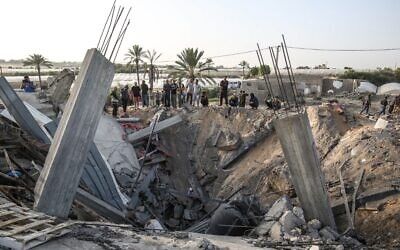 Palestinians gather around the remains of a house that the IDF says was used as a weapons cache controlled by the Palestinian Islamic Jihad, which was destroyed in an Israeli airstrike in Khan Yunis in the southern Gaza Strip November 13, 2019. (SAID KHATIB / AFP)