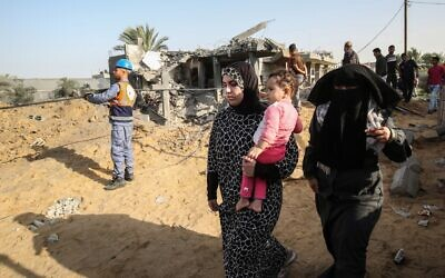Palestinian women walk past rescue teams and onlookers inspecting a house damaged in an Israeli air strike in Khan Yunis in the southern Gaza Strip November 13, 2019. (SAID KHATIB / AFP)