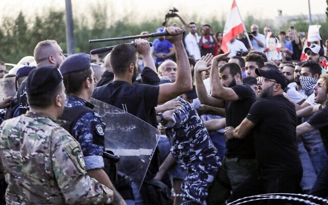 Lebanese demonstrators clash with anti-riot police on the road leading to the Presidential Palace in Baabda, on the eastern outskirts of Beirut on November 13, 2019, nearly a month into an unprecedented anti-graft street movement. (Anwar Amro/AFP)